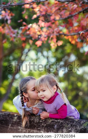 group of two little girls at autumn sunny day in park - stock photo