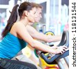 Group of two people in the gym, exercising their legs doing cardio cycling training - stock photo