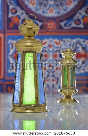 Group of Two Shiny Lanterns over Ramadan Fabric - stock photo