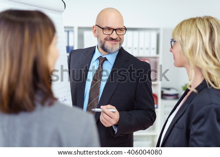 Group of two women and one smiling bearded man with eyeglasses meeting and discussing something next to chart in business office - stock photo