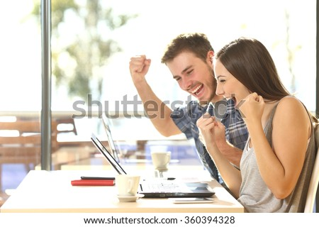 Group of two young euphoric students watching exam results in a laptop in a table of an university campus bar - stock photo