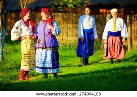 group of ukrainian people walking the village after folk festivities - stock photo