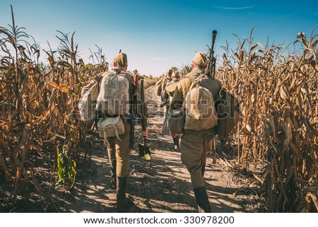 Group of unidentified re-enactors dressed as Soviet russian soldiers goes along field road. - stock photo