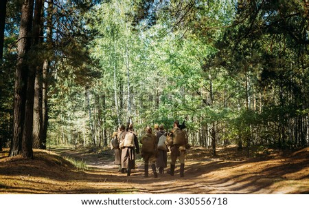 Group of unidentified re-enactors dressed as Soviet russian soldiers goes along forest road. - stock photo