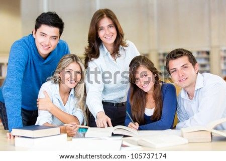 Group of university students at the library and smiling - stock photo