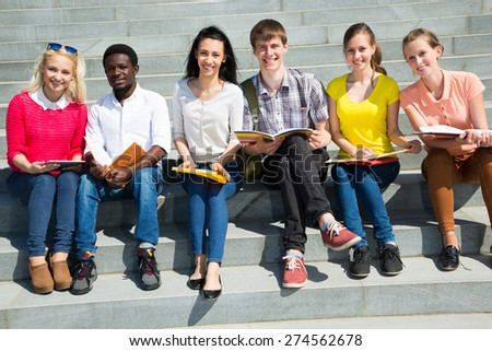 Group of university students studying reviewing homework - stock photo