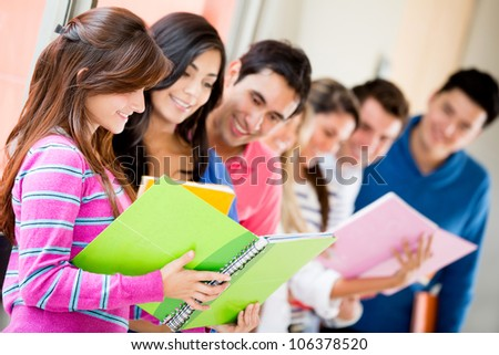 Group of univesity students sharing notes and smiling