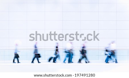 Group of unrecognizable business people in front of modern architecture, blurred motion