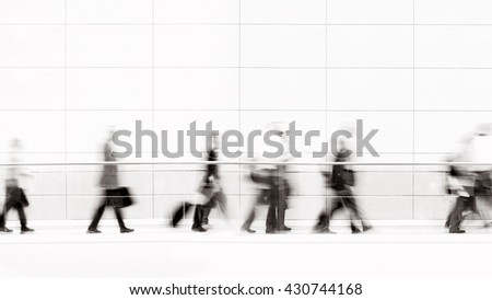 Group of unrecognizable business people in front of modern architecture, blurred motion, monochrome photo  - stock photo