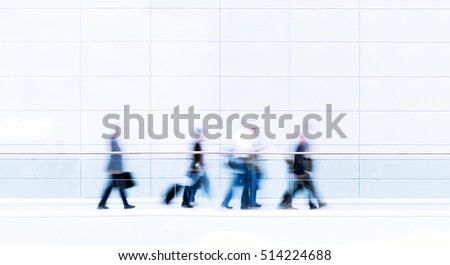 Group of unrecognizable business people in front of modern architecture, blurred motion, photo with copy space