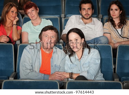 Group of upset audience watch movie in theater