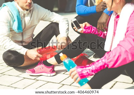 Group of urban runners making a break and taking some rest - stock photo