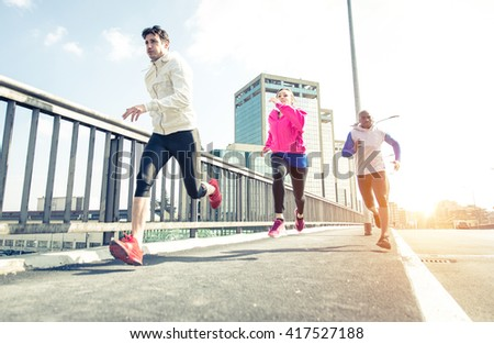 Group of urban runners making sport in an urban area. Three friends running in the morning on the city streets. Floor view, dynamic image - stock photo