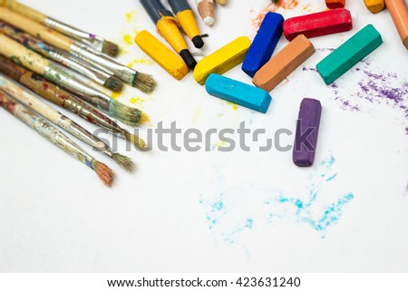 Group of used pastel chalk,color pencils and brushes over a white paper.Taken with selective focus and shallow deep of field. - stock photo