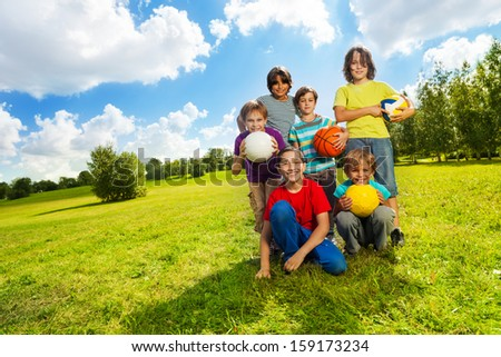 Group of very happy six boys, team sitting on the grass with balls and smiling, on sunny summer day - stock photo