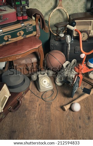 Group of vintage assorted items on attic hardwood floor with vintage wallpaper background.