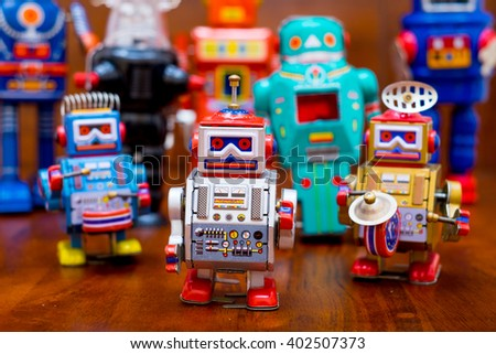 Group of vintage robots on a wooden floor (focus on the front robot)
