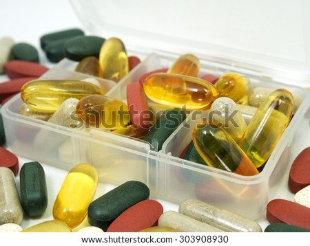 group of Vitamin with pill box,pill box,Vitamin,drug,multivitamin, herbal supplement capsules,fish oil,Natural organic green algae tablets,Colorful,pills and tablets, background - stock photo