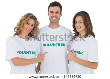 Group of volunteers pointing their tshirt on white background - stock photo