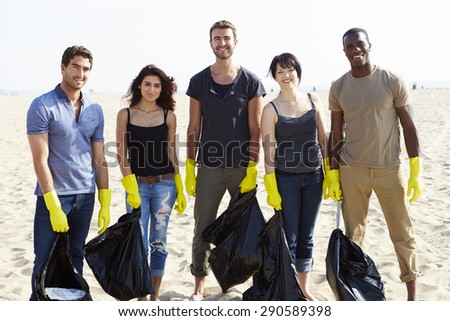 Group Of Volunteers Tidying Up Rubbish On Beach - stock photo