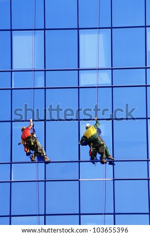 Group of washers wash the glass facade of modern skyscraper