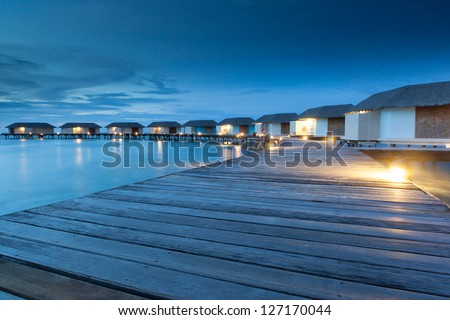group of water bungalow short after sunset, malediven - stock photo