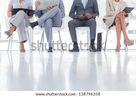 Group of well dressed business people waiting in waiting room - stock photo