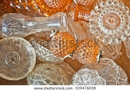 Group of white and brown crystal caps, rosettes, balloons, plates of retro chandeliers on a flea market table - stock photo