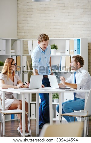 Group of white collar workers discussing ideas in office