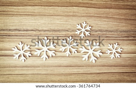 Group of white snowflakes on the wooden background. Symbol of winter.