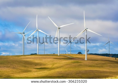 Group of wind turbines at a wind farm on a hill with cattle grazing beneath, creating renewable energy in Taralga NSW Australia. - stock photo