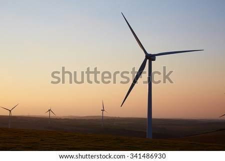Group Of Wind Turbines In Field At Dusk - stock photo