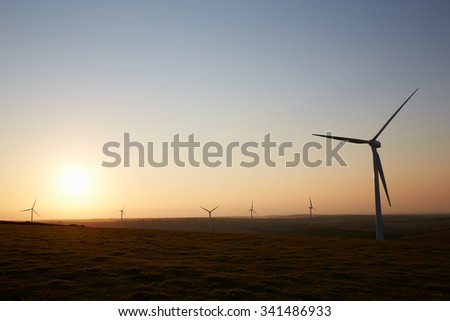 Group Of Wind Turbines In Field At Dusk
