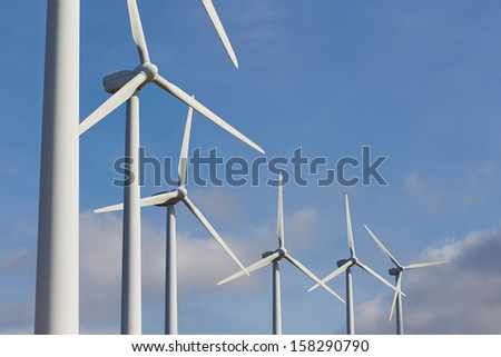 Group of windmills for renewable electric energy production on blue sky - stock photo