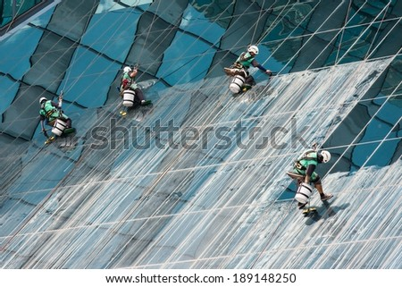 Group of window cleaners cleaning a high rise office building on a sunny day - stock photo