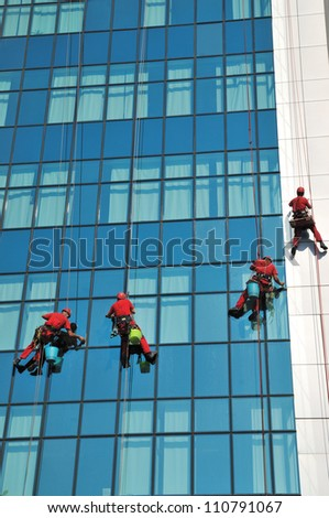 Group of windows washer cleaning the high building glass