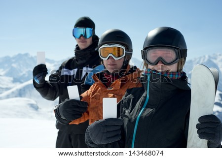 Group of winter sport people showing ski lift pass looking. Concept to illustrate ski admission fee - stock photo