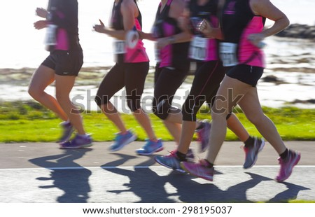 Group of woman compete in the race on coastal road. Blurred motion