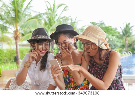 group of woman friend looking to smart phone and laughing with happiness face ,relaxing vacation of people lifestyle - stock photo