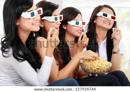group of woman friends watching movie wearing 3d glasses while having popcorn - stock photo