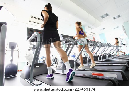 Group of women doing cardio exercises, running on treadmills in the gym - stock photo