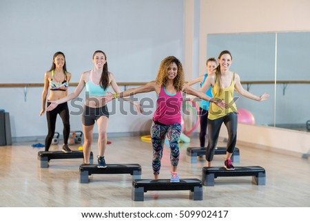 Group of women exercising on aerobic stepper in gym