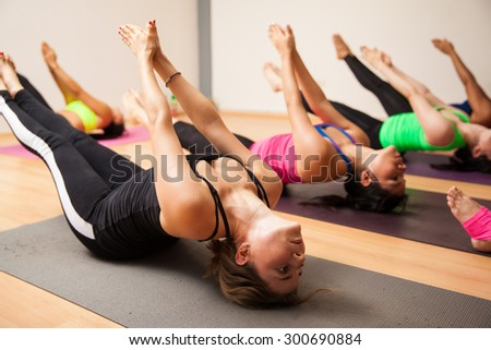 Group of women following their instructor during an authentic yoga class - stock photo