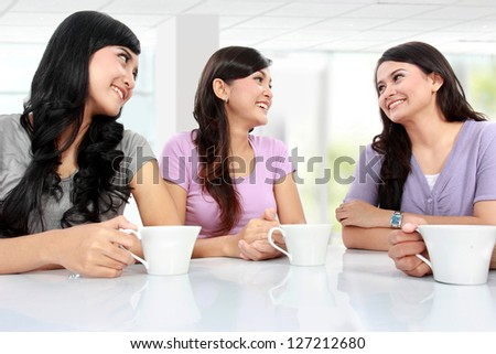 group of women friends chatting over coffee at home - stock photo