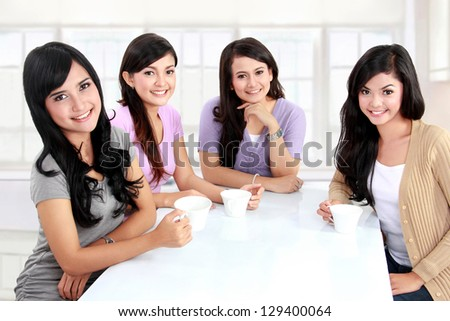 group of women friends having tea  together at home
