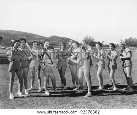 Group of women holding baseball bats and standing in a row - stock photo