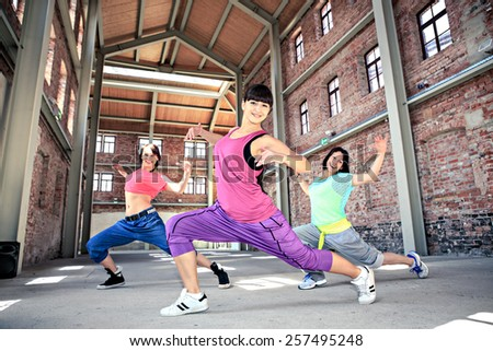 group of  women in sport dress dancing a fitness dance or aerobics - stock photo