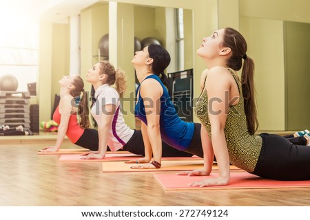 Group of women making step aerobics in the fitness class - stock photo