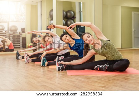 Group of women making stretching aerobics in the fitness class - stock photo