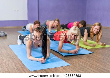 group of women practicing the side plank yoga pose during a class in a gym